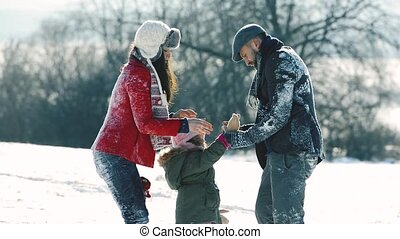 Father, mother and their daughter having fun in winter...