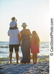 Father, mother and two daughters standing on the sand and admiring the sea.