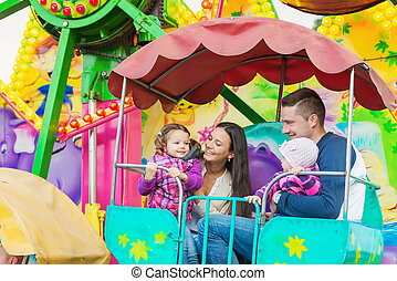 Father, mother, daughters enjoying fun fair ride, amusement...