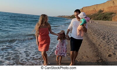 Father, mother , little girl and baby walking along the beach in slow motion