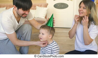 Father of happy family celebrating birthday dress hat to son at home
