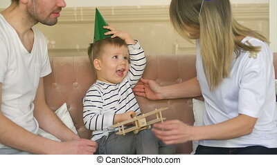 Father of happy family celebrating birthday present gift to his son at home