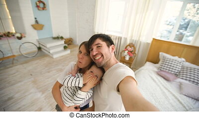 Father of happy family taking selfie video on camera in bedroom