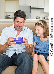 Father opening gift given by daughter while sitting on sofa at home