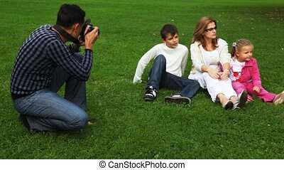 father photographs family from mother and daughter with the son sits on field in park