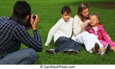 father photographs mother and daughter with the son sits on field in park