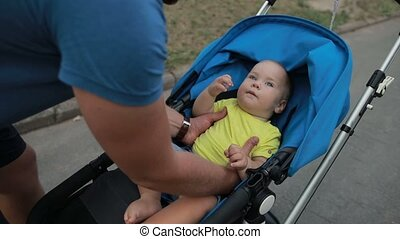 Father picking up toddler son from baby carriage