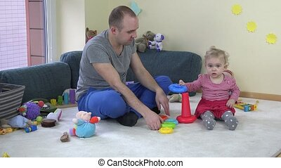 father play with baby daughter with colourful tower in room. 4K