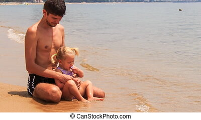 father play with little girl sitting on edge of water on beach