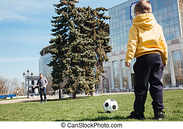 Father playing football with his little son outdoors in park.