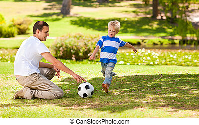 Father playing football with his so