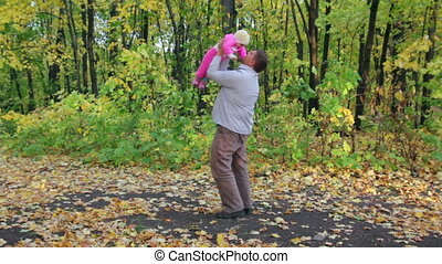 father playing with baby in autumn park