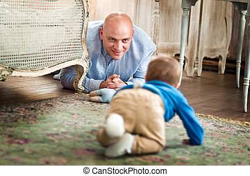 father playing with baby on the floor at home