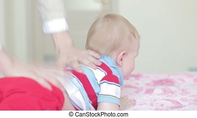 father playing with baby son at home