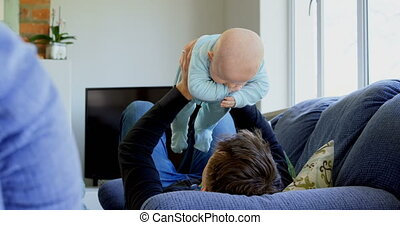 Father playing with his baby boy in living room 4k