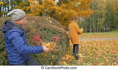 Father playing with his daughter in the autumn park. However, they smile and laugh. Dad throws leaves on the head of a teenager.