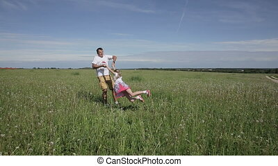 father playing with his daughter in field