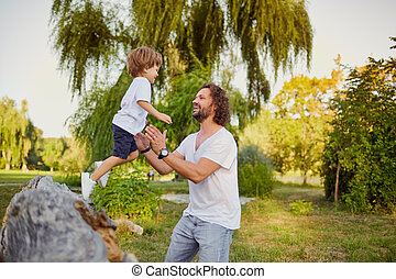 Father playing with his son in the park.