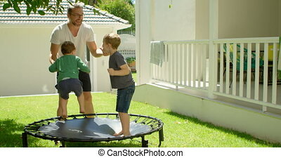 Father playing with kids on trampoline 4k