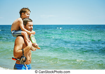 father playing with son at sea