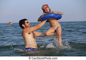 father plays with his daughter in the sea during the summer holidays