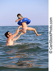 father plays with his daughter in the sea