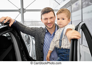 Father posing with son near auto in car dealership.