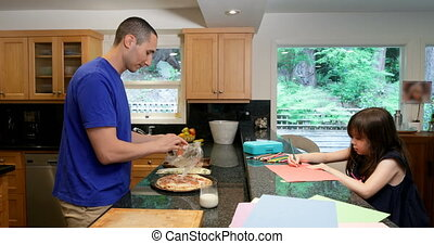 Father preparing food while daughter drawing on paper in kitchen 4k