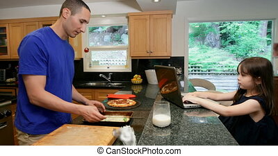 Father preparing food while daughter using laptop in kitchen 4k