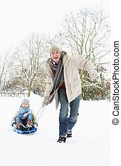 Father Pulling Son On Sledge Through Snowy Landscape
