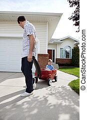 Father Pulling Son Sitting in Wagon - Father pulling son in...