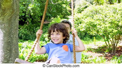 Father pushing his young son on a swing on a sunny day