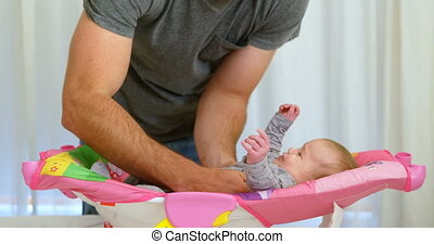 Father putting his baby on baby boy bed 4k