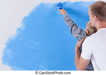 Father raising his son during painting the wall