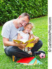 Father reading a book to his daughter while laying on the grass in the garden