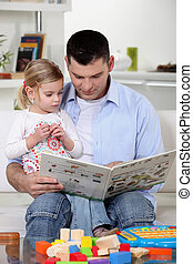father reading a book to his little girl