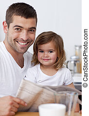 Father reading a newspaper in the kitchen - Portrait of...