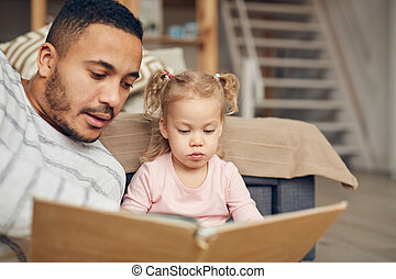 Father Reading Book to Cute Daughter
