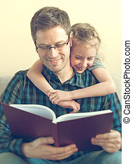 Father reading book with daughter at home.