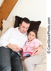 Father reading his daughter a story