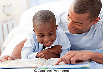 Father reading with his son in bedroom