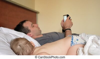 Father reads the news on the tablet near the sleeping baby. A boy resting in the foreground of a house on a bed