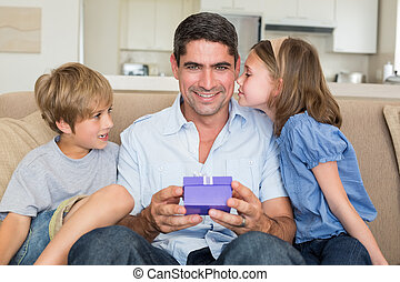 Father receiving gift from loving c