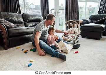 Father Relaxing with his Daughters at Home