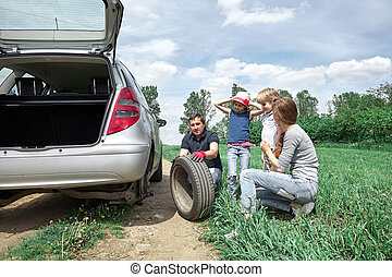 father replaces the damaged tire of the family car.