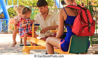 father rocks little girls on double swing mother takes pictures