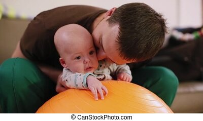 Father rolls newborn on fitness ball sport massage