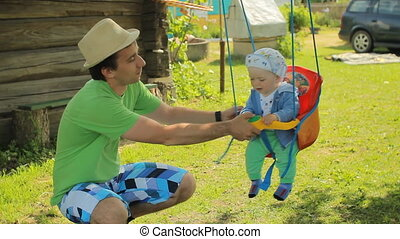 Father rolls the beautiful baby on a swing. Yang man with his son in the garden of his home