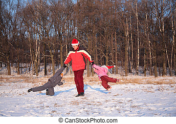 father rotate children in wood in winter