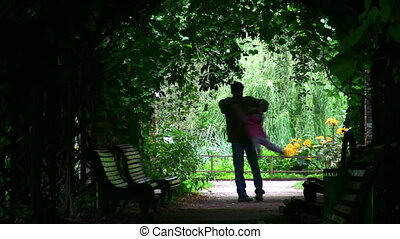 father rotate girl silhouette in plant tunnel